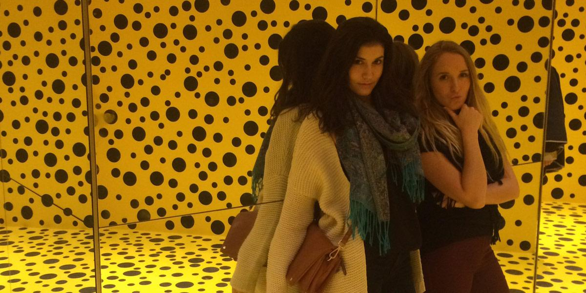 Students posing in front of a mirror reflecting bright polka dot covered walls