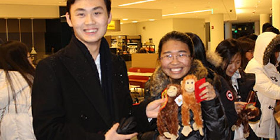Students holding cards, tokens, and toy monkeys