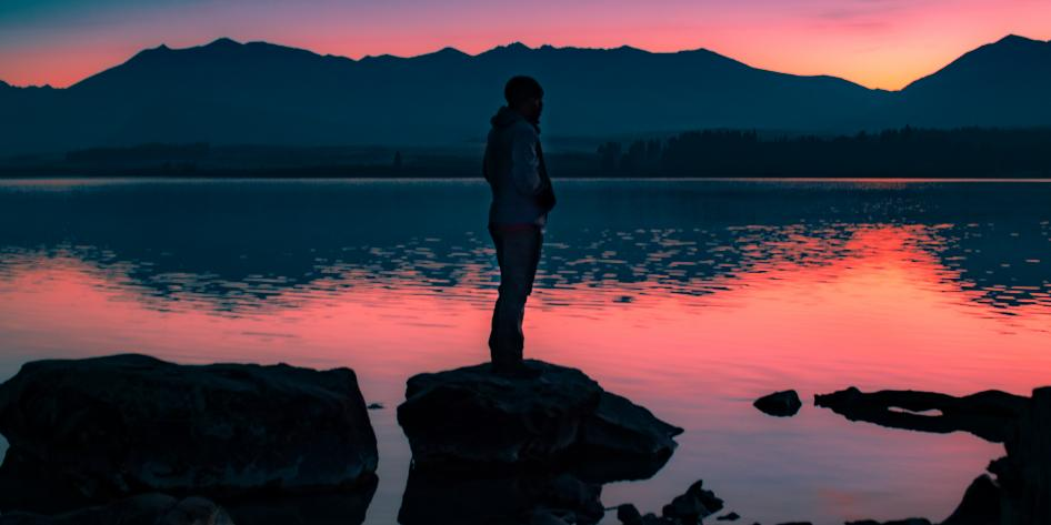 A study abroad student stands on a rock in the middle of water during sunset
