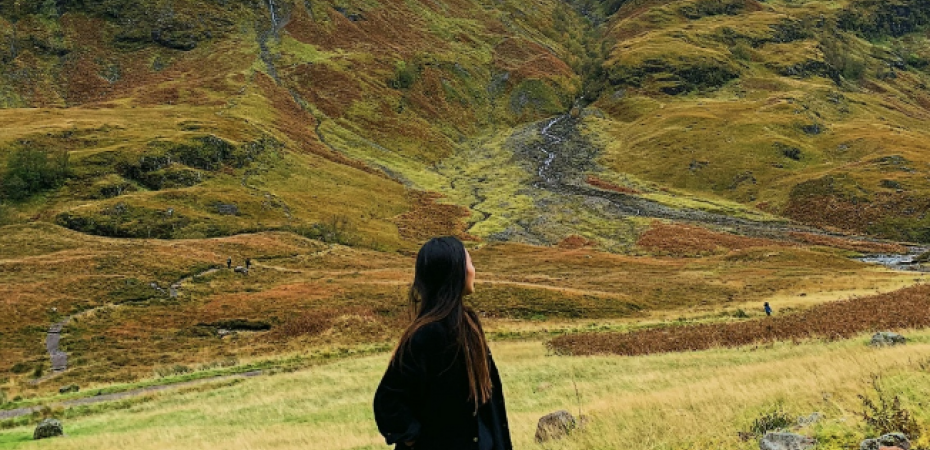 A study abroad student looks at mountains in the landscape before her