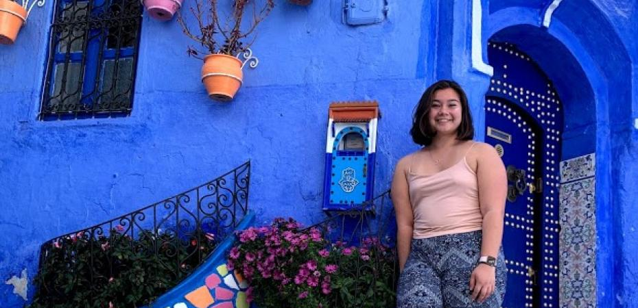 A student stands against a blue building during her study abroad