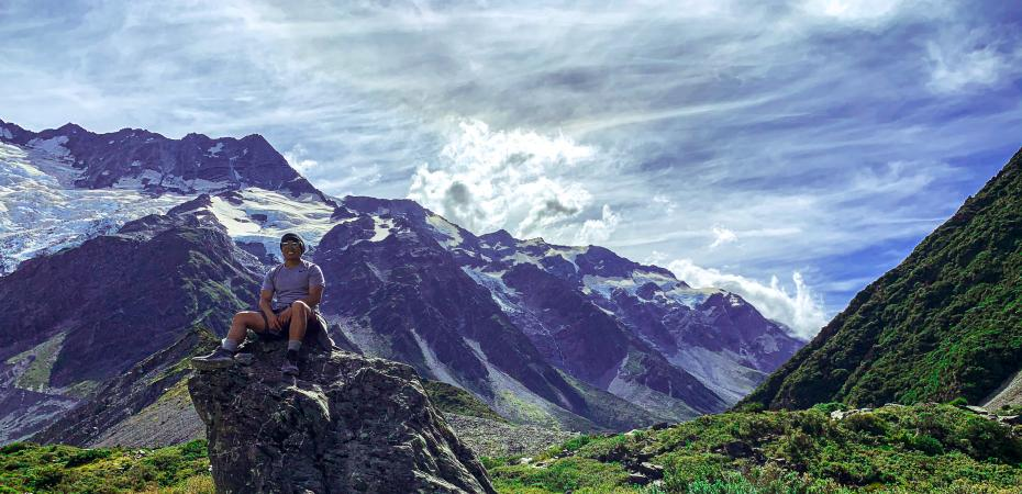 Joshua Hsia sits on a hill with mountains behind him in New Zealand