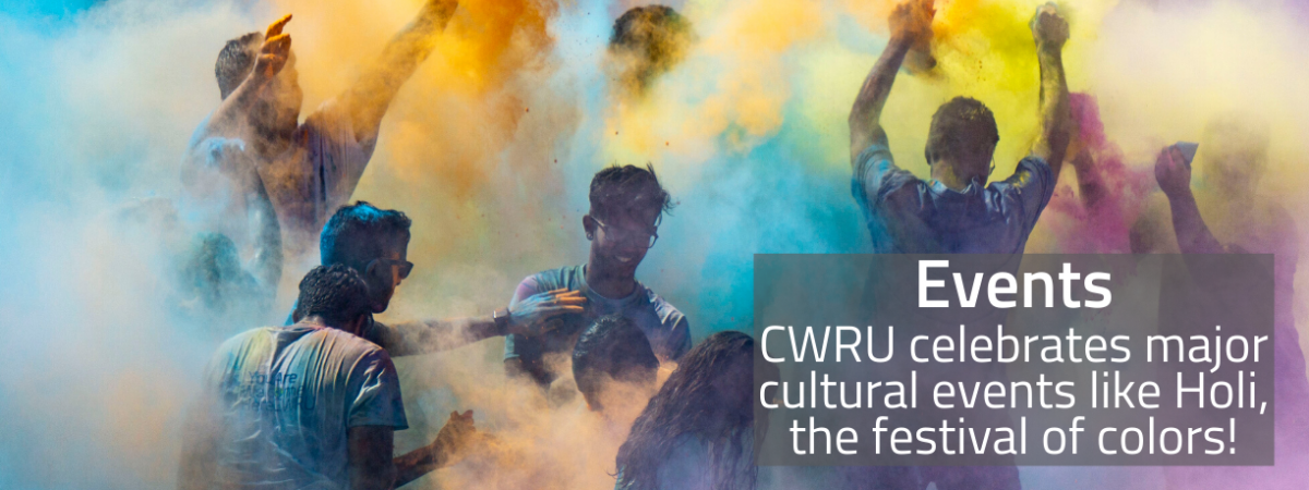 A group of CWRU students surrounded by clouds of colored powder during the 2019 Holi festival