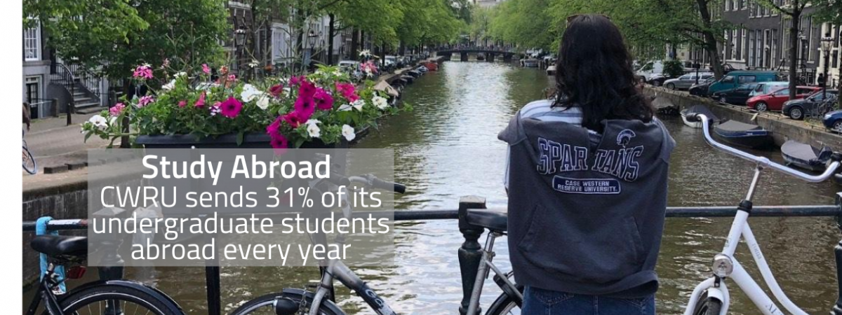 Study Abroad/ CWRU sends 31% of its undergraduate students abroad every year/ A picture of a CWRU student standing in front of a river in the Netherlands wearing a CWRU sweatshirt