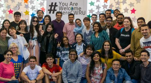 A group picture of international students at CWRU standing in front of a #YouAreWelcomeHereCWRU sign in Tomlinson Hall