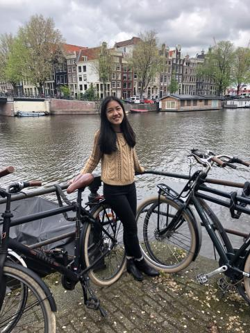 Annie Du standing with a bicycle in front of a body of water while studying abroad at Kings College London