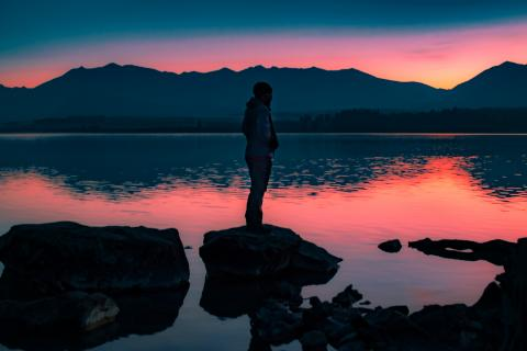 A student stands on a rock in water with mountains behind it at sunrise