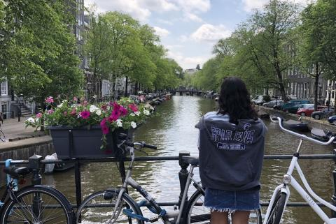 A student with a CWRU shirt on looks at a river between two rows of buildings and trees