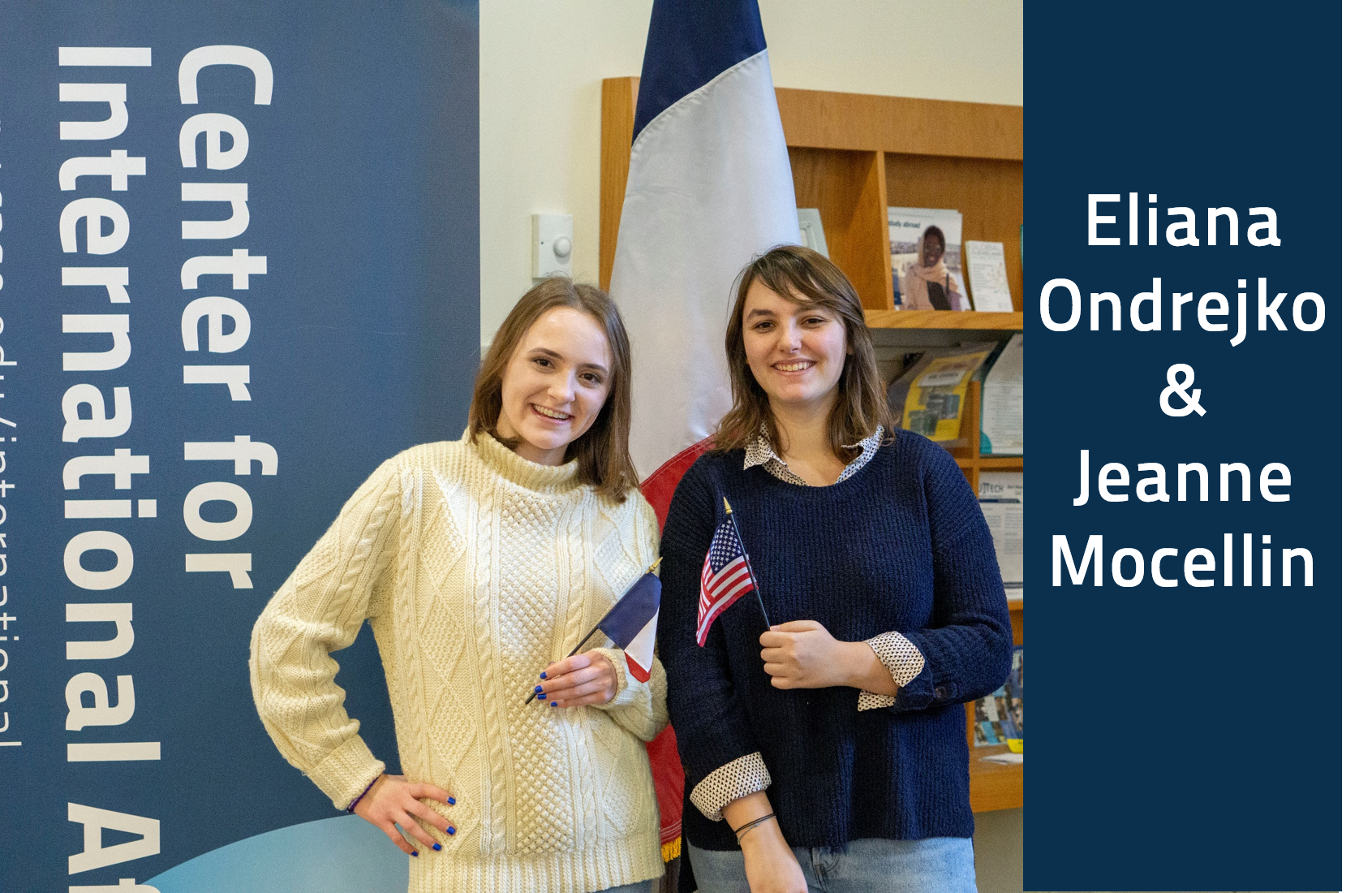 A picture of Eliana Ondrejko and Jeanne  Mocellin standing in front of a French flag, each holding a flag from their home country. Jeanne is holding the French flag and Eliana is holding the American flag.