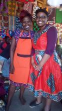 A picture of Gabrielle standing with a tailor in the Luwero District of Uganda, who altered Gabrielle's brightly-colored dress in less than five minutes