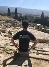A picture of Michel Yuzik sitting with his back facing the camera, wearing a #YouAreWelcomeHereCWRU shirt during his study abroad