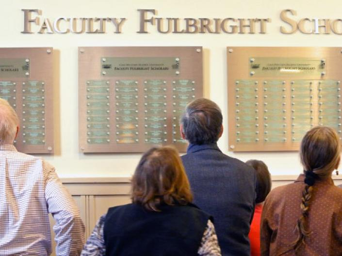 Faculty members looking at the plaques of the Fulbright winners on the wall on campus