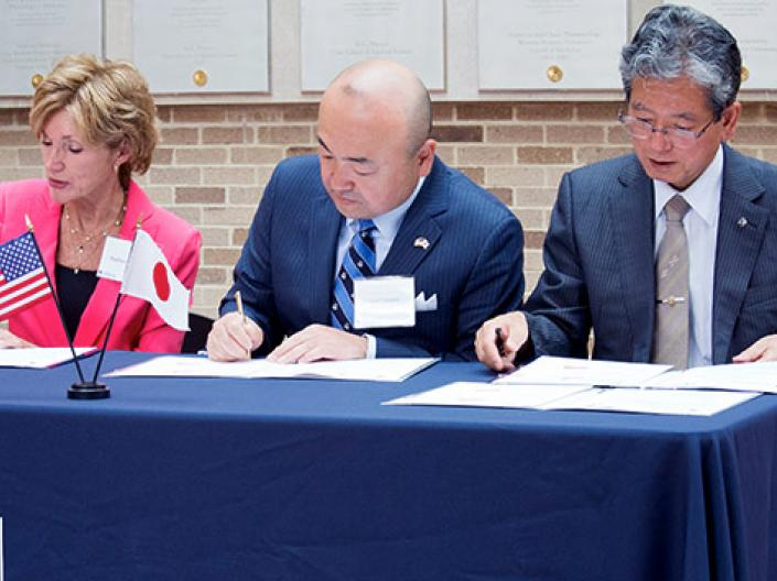 President Snyder signing paperwork with representatives from Japan