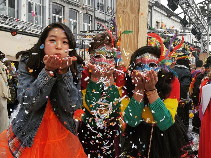 Students at carnival in Netherlands blowing confetti