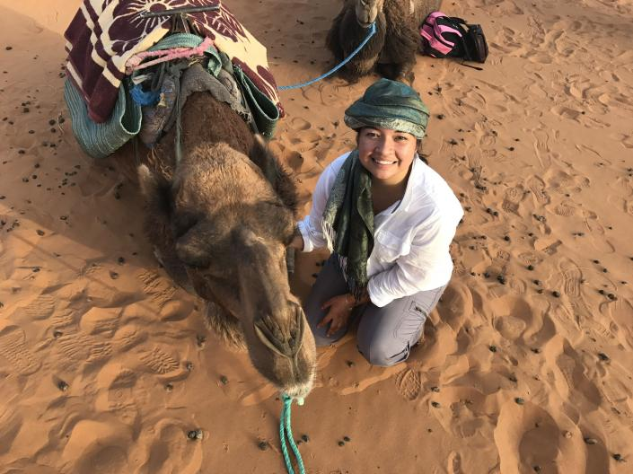 CWRU study abroad student pictured with a camel in the desert.