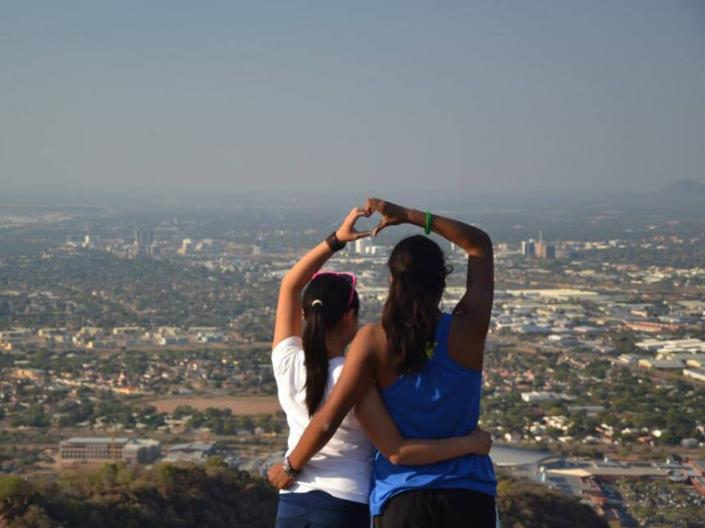 2 CWRU Students on a Hilltop looking out over a city with linked arms