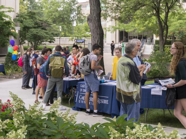 A photo of students visiting information tables at the 2018 Study Abroad Fair held outside on the main quad at CWRU