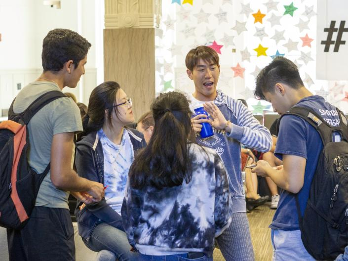 CWRU international students talking in a circle inside Tomlinson Hall