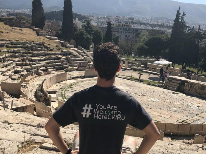Michel Yuzik sitting outside with a #YouAreWelcomeHereCWRU tee shirt on
