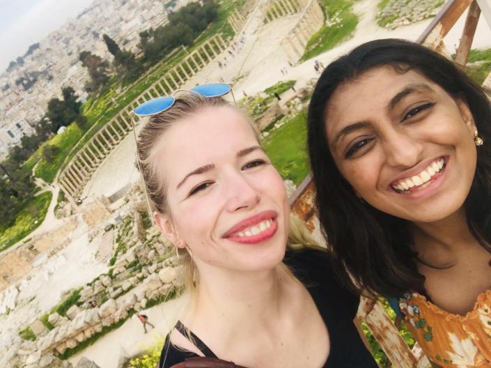 Two female CWRU students stand together smiling outside during a study abroad trip