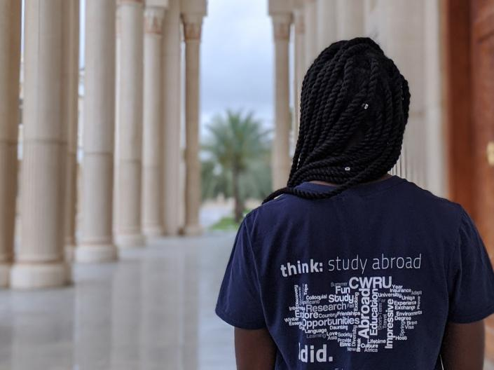 A female CWRU student stands with her back turned to the camera wearing a CWRU study abroad tee shirt