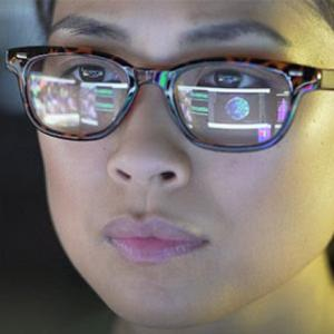 Image of a computer screen reflected in a closeup of a women's face wearing glasses