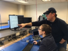 Instructor pointing to computer screen as female student looks on