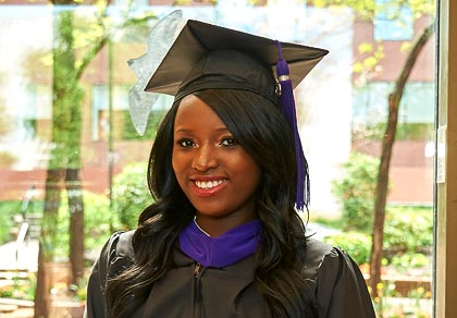 law student in black graduation robes with purple stole and tassle