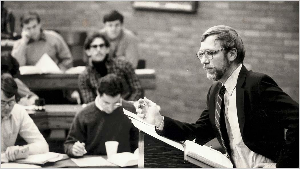Black and white image of Professor Emeritus Arthur Austin lecturing with students in background
