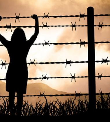 Woman holding onto a barbed wire fence
