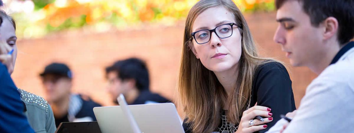 two law students studying outside with a laptop, with other students in background