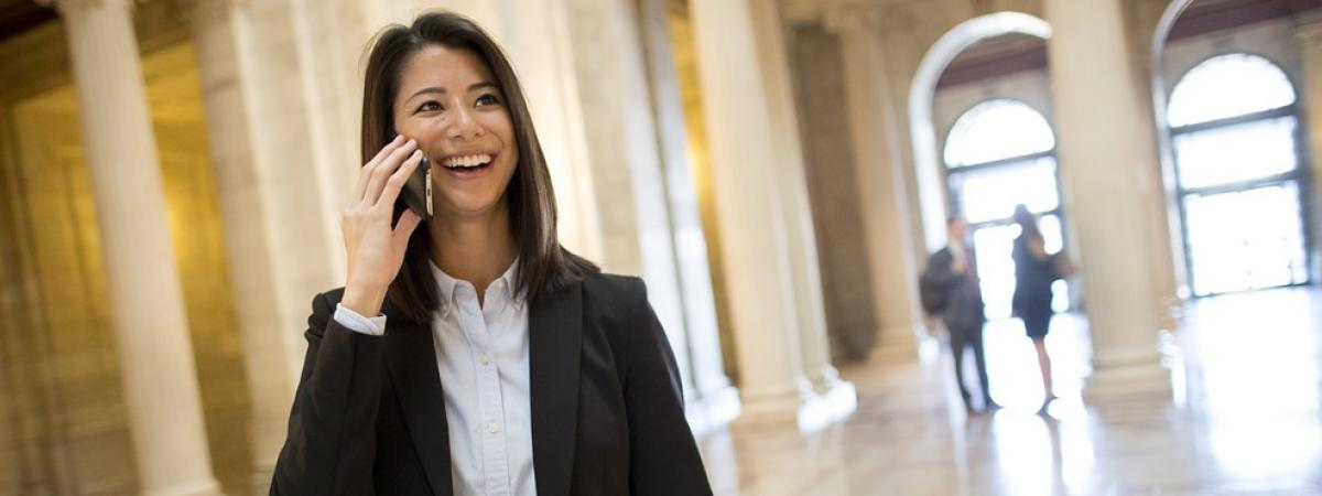 law student smiling on cell phone in lobby of large building