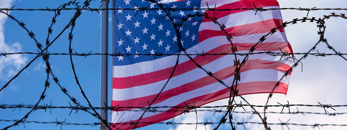 An american flag with barbed wire in front of it