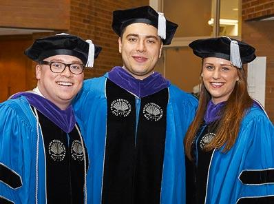 Three PhD graduates stand for a photo