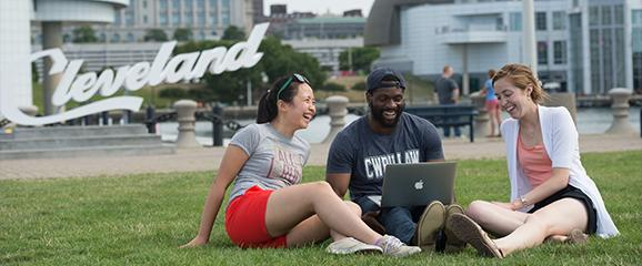three case western reserve university students sitting on the grass in front of the rock and roll hall of fame in downtown cleveland