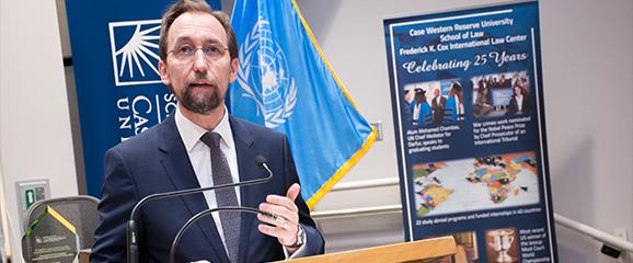 speaker giving a presentation behind a lecturn, with a case western reserve university banner in front and back wall, and united nations flag in background