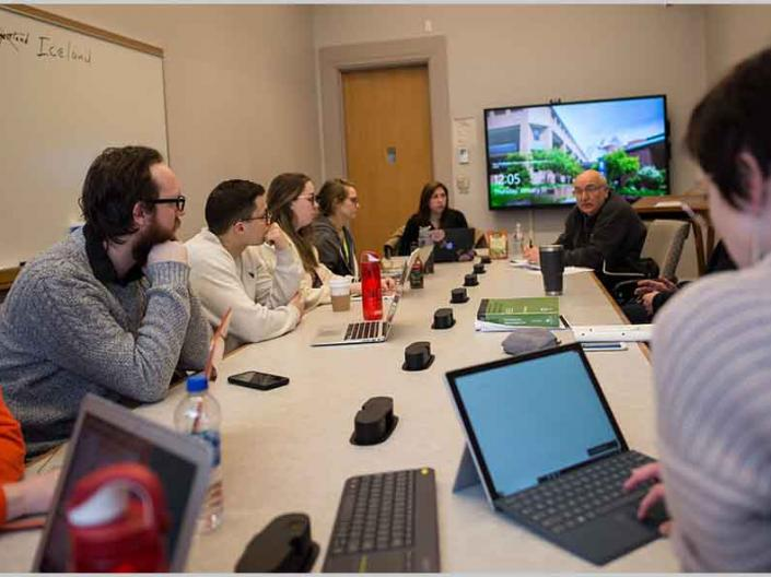Students and professor sitting around large table with laptops with a large video screen in background