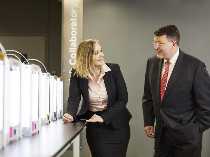 Student Rebecca Lindhorst and Professor Ted Theofrastous speak near a set of 3D printers.