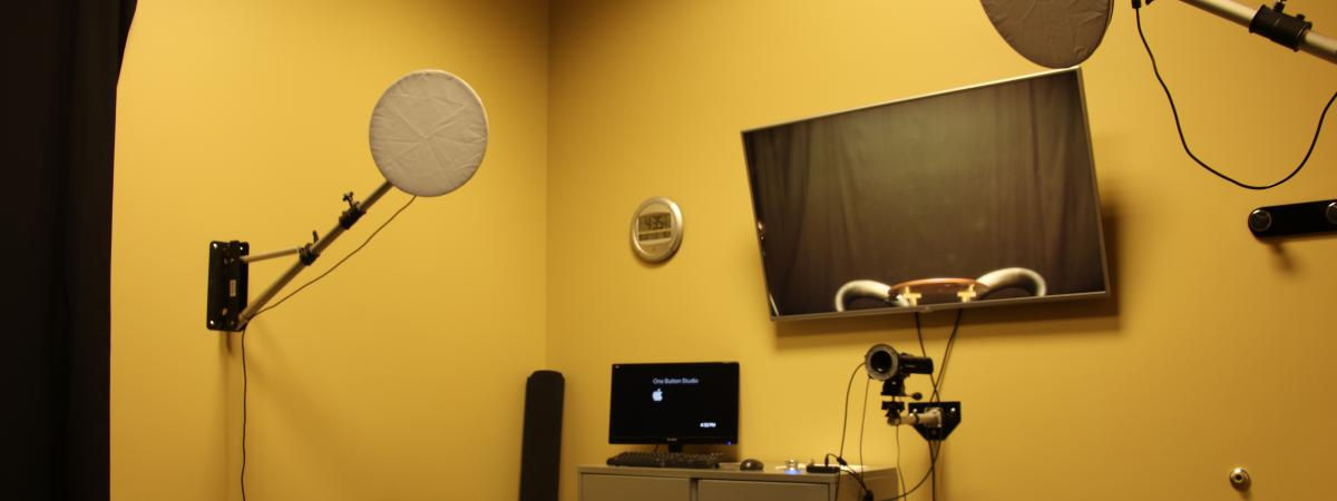 A video recording studio with lighting, screens, and a microphone.