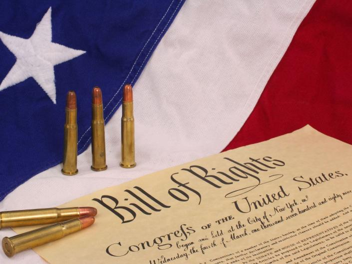 an american flag with bullets and the bill of rights in front of it