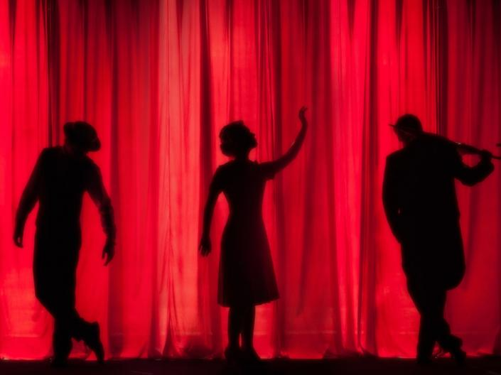 three silhouettes in front of a red curtain at a theatre