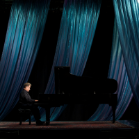 Jeffrey Siegel playing piano with a curtain behind him