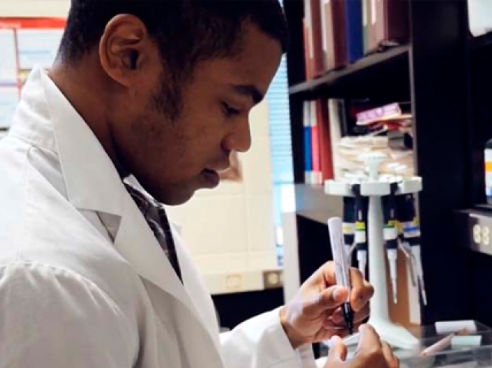 CWRU PREP student works in a white lab coat conducting research at black lab bench