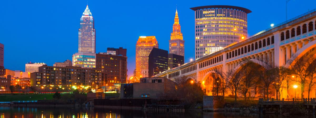 Downtown Cleveland skyline at dusk with a bridge on the left and the Cuyahoga River with skyline reflections below.
