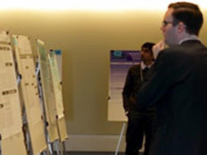 Man looking at display posters with another man in the background