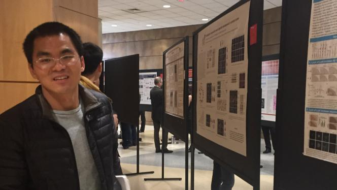A postdoctoral fellow next to a poster