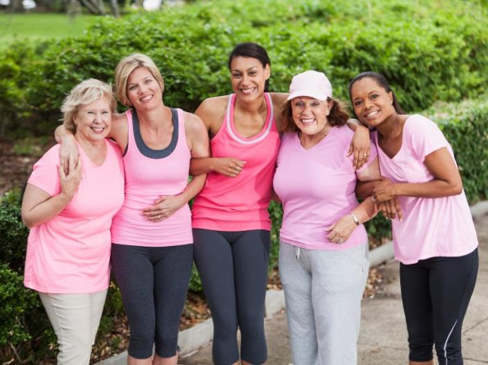Five women in pink shirts pose together for a photo