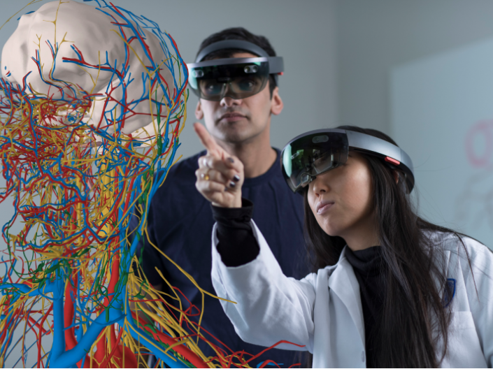 Two students using hololens equipment to analyze the human nervous system