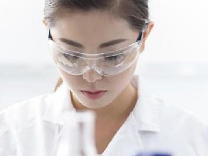 Image of researcher in white labe coat and safety goggles, looking down in analysis.  There are the tops of three pieces of lab equipment, one white and two with blue tops, in the foreground