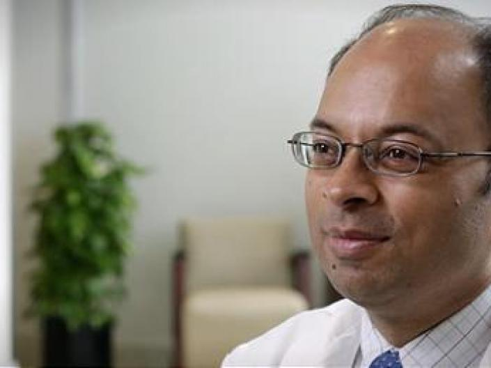 Image headshot of Dr. Mukesh K. Jain, door, medium sized potted plant, and biege chair with brown arms in the background